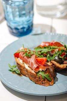Bruschetta avec baguette noire, jamon, roquette et tomate sur une table en carrelage blanc, lumière du soleil dure et lumineuse. une collation saine et élégante.