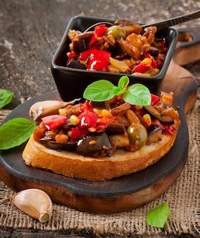Bruschetta caponata aux raisins secs et pignons de pin décorée d'une feuille de basilic