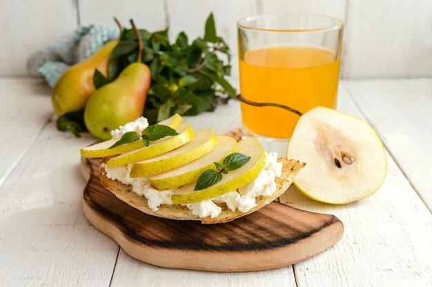 Bruschetta avec fromage à pâte molle, poire juteuse et un verre de jus de fruits frais. petit-déjeuner éco. menu de remise en forme