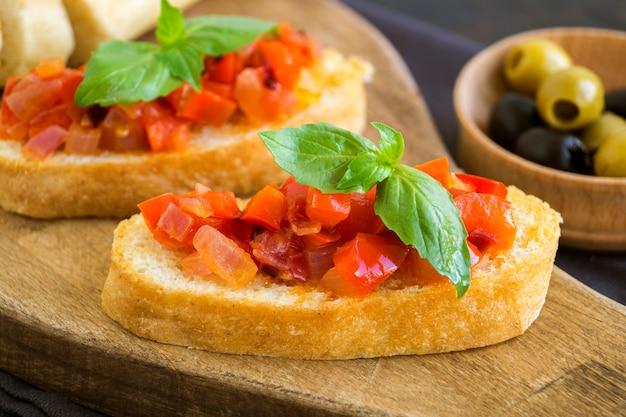 Bruschetta italienne traditionnelle avec tomates, poivrons et basilic