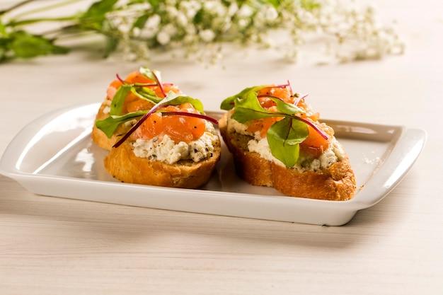 Bruschetta avec mangue hachée, cresson et fromage de chèvre sur baguette fraîche sur la table