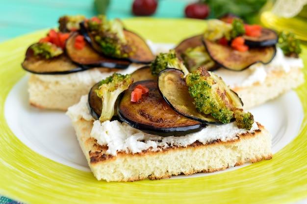 Bruschetta parfumée au fromage feta, tranches d'aubergines et brocolis grillés. fermer