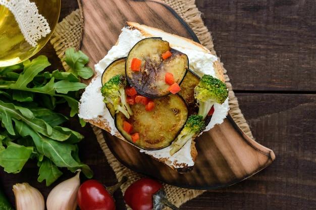 Bruschetta parfumée au fromage feta, tranches d'aubergines et brocolis grillés. la vue de dessus
