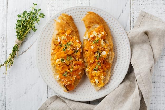 Bruschetta avec potiron cuit au four, fromage feta et thym sur une surface en bois clair. sandwich épicé à la citrouille. mise au point sélective.