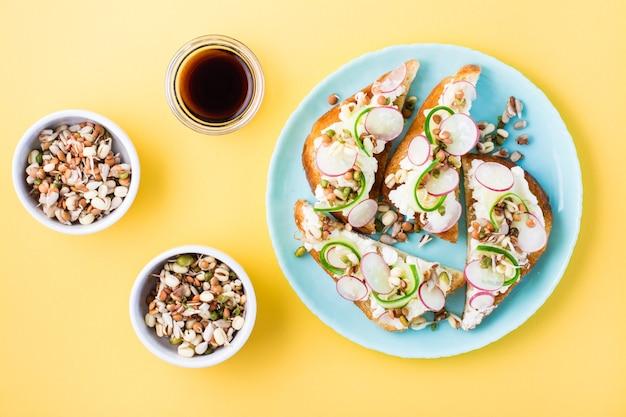 Bruschetta prête à manger avec fromage blanc, légumes et grains germés sur une assiette sur une table jaune.