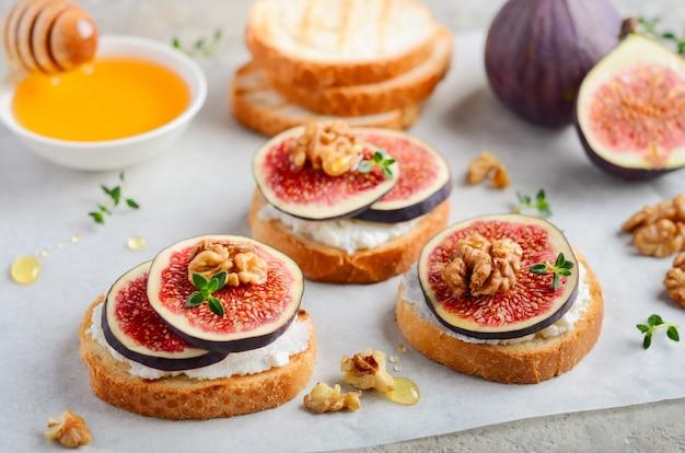 Bruschetta à la ricotta fraîche, aux figues, aux noix, au thym et au miel sur du béton gris.