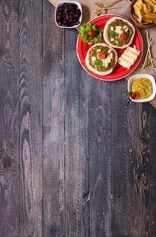 Bruschetta savoureuse et délicieuse avec avocat, tomates, fromage, herbes, chips et liqueur, sur un fond en bois.