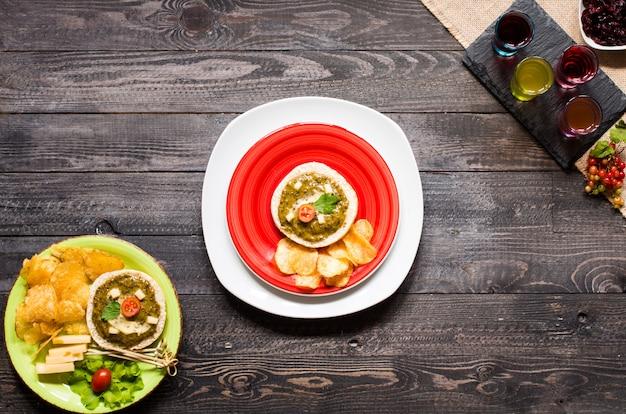 Bruschetta savoureuse et délicieuse avec avocat, tomates, fromage, herbes, chips et liqueur