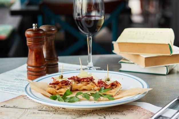 Bruschetta sur une table en bois dans une assiette blanche et un verre de vin rouge