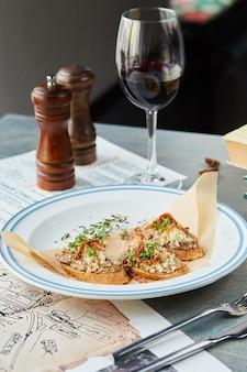 Bruschetta sur une table en bois dans une assiette blanche et un verre de vin