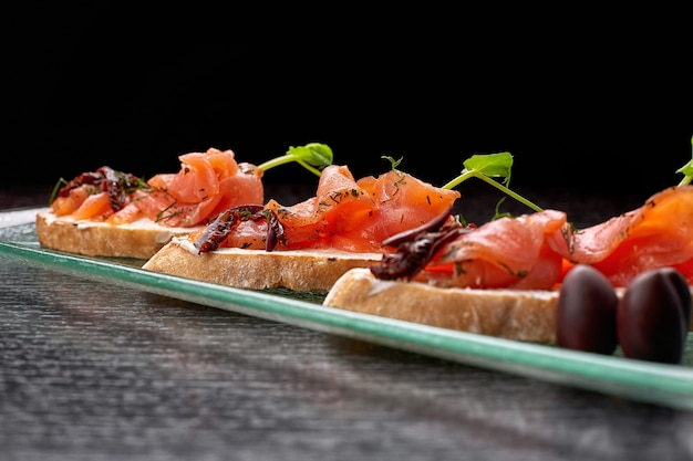 Bruschetta à la truite, saumon, fromage à la crème et microgreen sur une assiette en verre