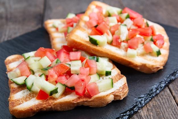 Bruschettas au pain végétarien avec concombre et tomates fraîches.