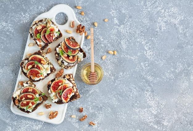 Bruschettas aux figues avec ricotta, noix et miel sur table en pierre.