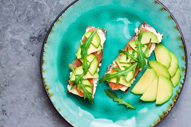 Bruschettas prêtes à consommer avec du saumon, du beurre, de l'avocat et de la roquette sur une assiette