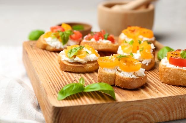 Bruschettas savoureuses aux tomates sur planche de bois