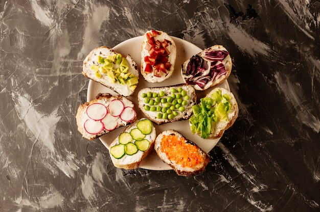 Brushetta ou tapas espagnoles traditionnelles. des amuse-gueules aux antipasti italiens sur une planche de bois.