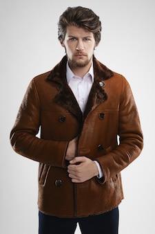 Brutal bel homme mal rasé avec barbe et moustache en manteau en peau de mouton avec col en fourrure