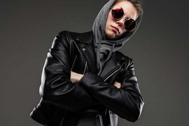 Brutal caucasian girl avec des traits du visage rugueux dans une veste noire avec un capuchon isolé sur mur noir