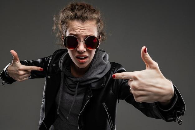 Brutal caucasian girl avec des traits du visage rugueux dans une veste noire isolée sur mur noir