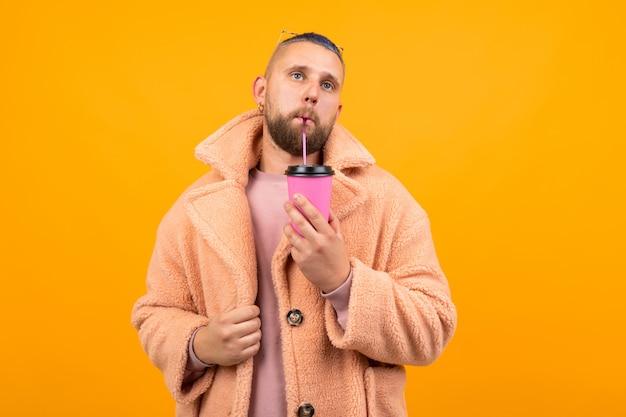 Brutal caucasian man aux cheveux bleus courts et lunettes rouges dans un manteau de fourrure boit du café et attend quelque chose isolé sur orange