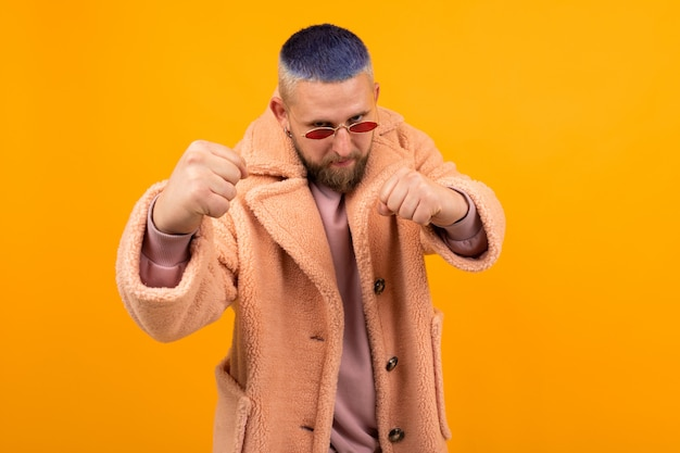 Brutal caucasian man with short blue hair and red glasses in a fur coat boxing isolated on orange