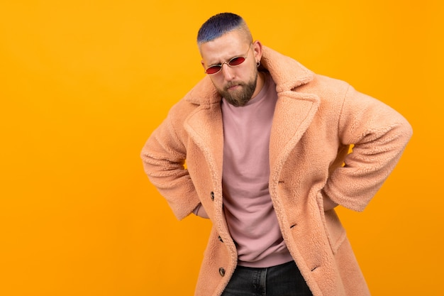 Brutal caucasian man with short blue hair et red glasses in a fur coat gesticulate isolated on orange