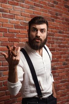 Brutal jeune bel homme fumant le cigare sur le mur de briques.