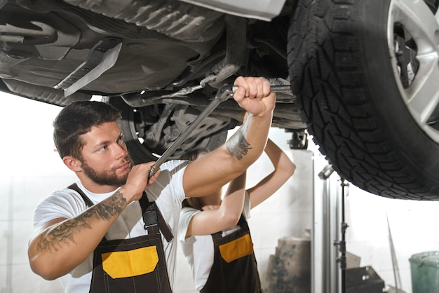 Brutal man repairing automobile with woman in autoservice.