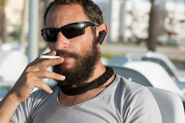 Brutal russe caucasien beau mec cool blanc fumant des lunettes de soleil et un t-shirt gris dans un café. homme américain avec une cigarette à la main. bel homme juif moustache et barbe, gros plan