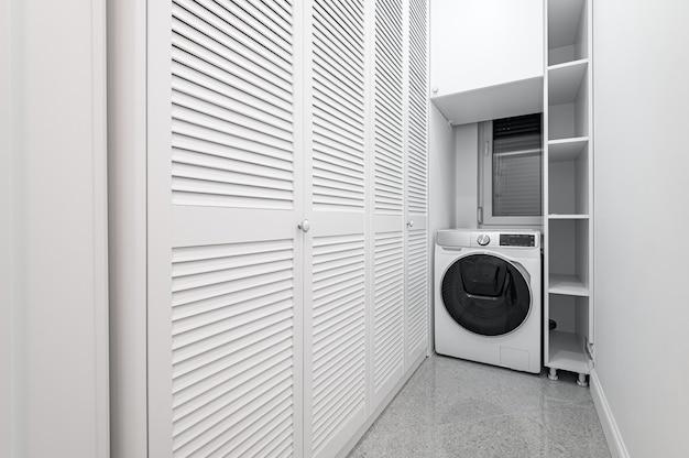 Buanderie blanche avec placard dans nouvel appartement