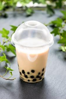 Bubble boba tea avec du lait et des perles de tapioca dans une tasse en plastique