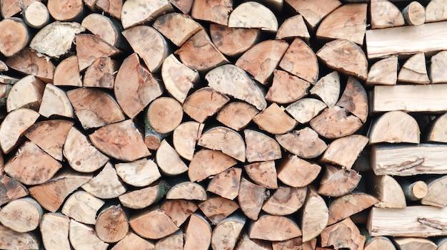 Une bûche soigneusement pliée de bois coupé. le feu fond. bois de chauffage empilés les uns sur les autres. le bois de chauffage est collecté pour le chauffage par temps froid. texture de fond de bois de chauffage sec empilé.