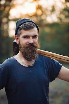 Un bûcheron barbu brutal avec une longue barbe et moustache dans un t-shirt et un chapeau chaud avec une hache sur son épaule