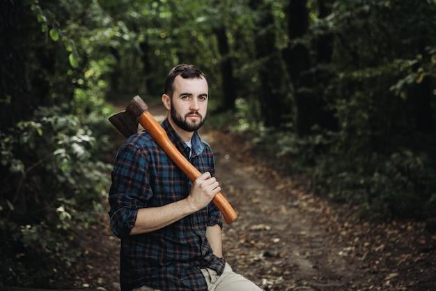 Bûcheron barbu fort tenant une hache dans les bois