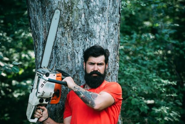 Bûcheron avec hache ou tronçonneuse dans la déforestation de la forêt d'été beau jeune homme avec hache près de ...