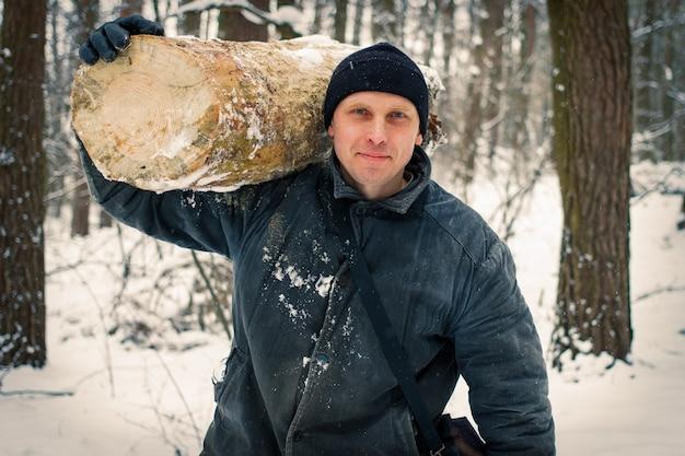 Le bûcheron tient un tronc d'arbre dans la forêt