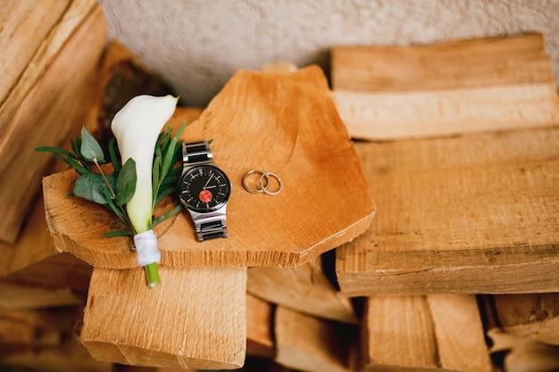 Bûches de bois contre le mur avec des anneaux de mariage, une montre-bracelet pour homme et une fleur à la boutonnière de calla.