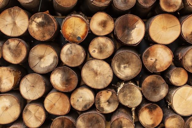 Bûches fendues rondes empilées en rangées texture bois.