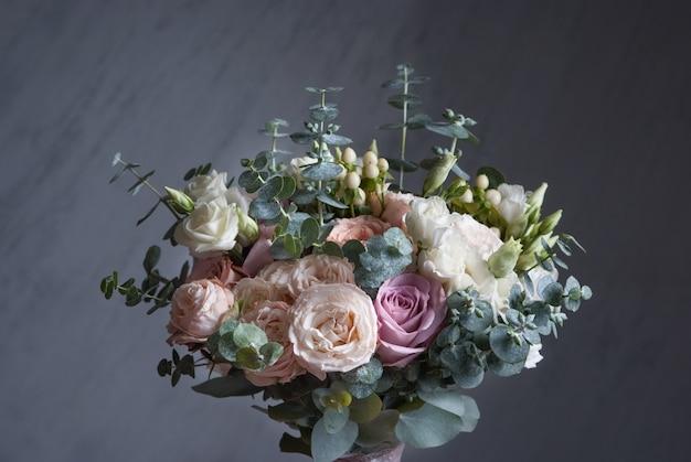 Buequet de mariage avec des roses blanches sur fond gris. fermer