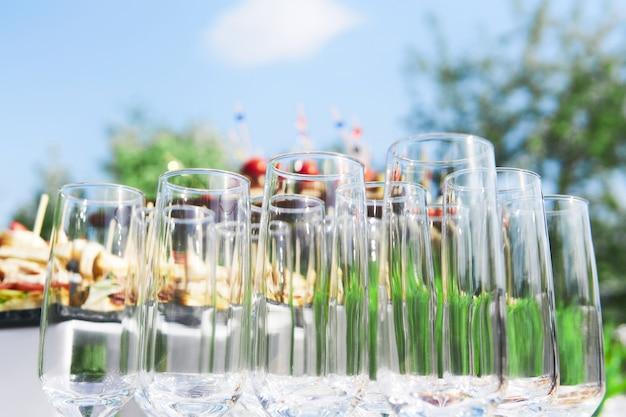 Buffet en plein air - verres vides sur fond de collations froides contre le ciel en attente d'invités