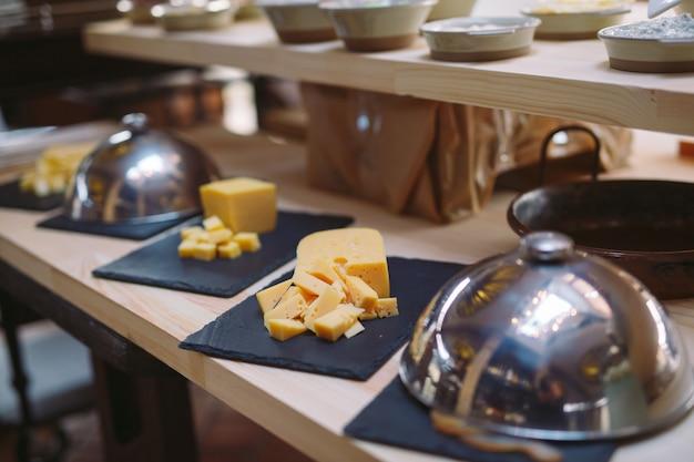 Buffet. le serveur est titulaire d'une assiette de fromage en tranches.
