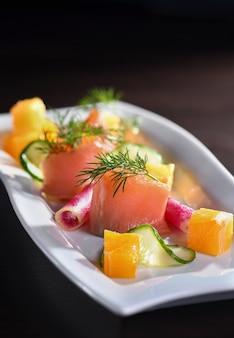 Buffet de tranches de saumon mariné avec radis, concombre et cubes d'orange
