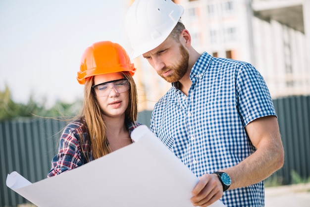 Builder femme et homme à blueprint