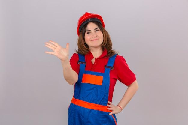 Builder femme portant des uniformes de construction et un casque de sécurité heureux en agitant la main dans le geste de salutation donnant cinq à un ami sur un mur blanc isolé