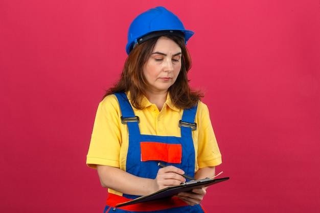 Builder femme portant des uniformes de construction et un casque de sécurité tenant le presse-papiers en le regardant avec un visage sérieux sur un mur rose isolé