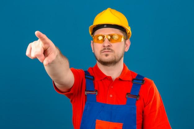 Builder homme portant des lunettes uniformes de construction et un casque de sécurité pointant avec le doigt sur quelque chose en face de lui avec un visage sérieux debout sur un mur bleu isolé