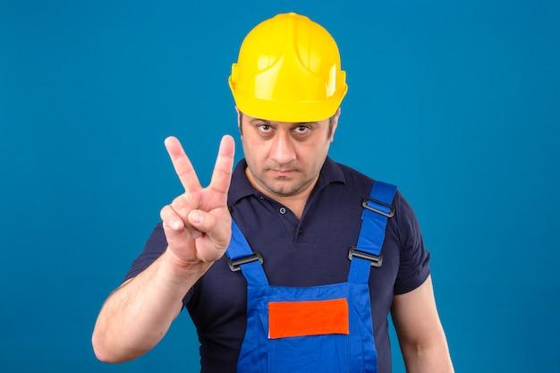 Builder homme portant l'uniforme de construction et un casque de sécurité et pointant du doigt comme intimidation sur mur bleu isolé