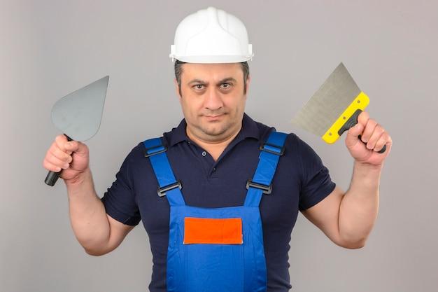 Builder homme portant des uniformes de construction et un casque de sécurité debout avec un couteau à mastic et une truelle dans les mains avec un visage sérieux sur un mur blanc isolé