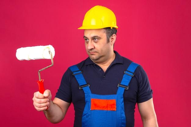 Builder homme portant des uniformes de construction et un casque de sécurité debout avec rouleau à peinture à l'écart sur mur rose isolé