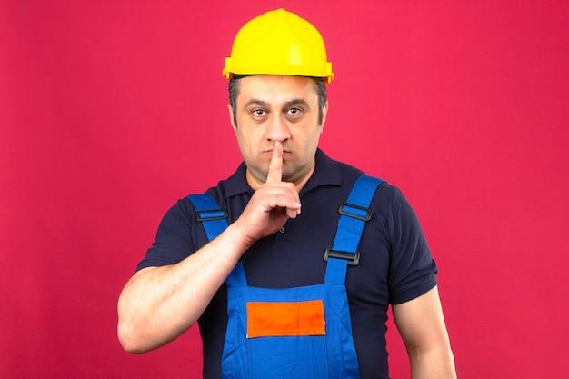 Builder homme portant des uniformes de construction et un casque de sécurité faisant un geste de silence avec l'index sur les lèvres avec un visage sérieux sur un mur rose isolé